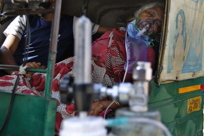 Un donna malata di COVID-19 respira con l'aiuto di una maschera di ossigeno in un risciò, attende di essere ricoverata in ospedale, ad Ahmedabad, in India (AP / Ajit Solanki)